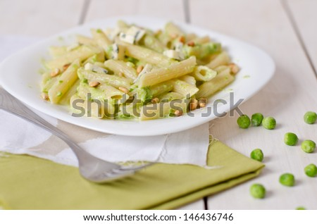 Pasta with peas, cheese and pine nuts - stock photo