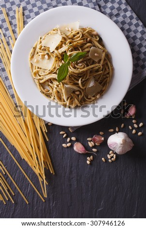 pasta with pesto, pine nuts and parmesan cheese on a plate and ingredients on the table. vertical top view - stock photo