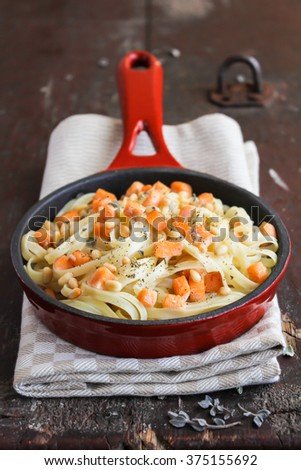Pasta with roasted salmon and thyme in cream sauce in a pan, selective focus - stock photo