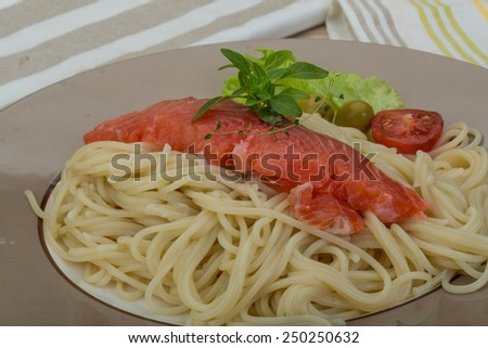 Pasta with salmon and basil on the wooden bakground - stock photo
