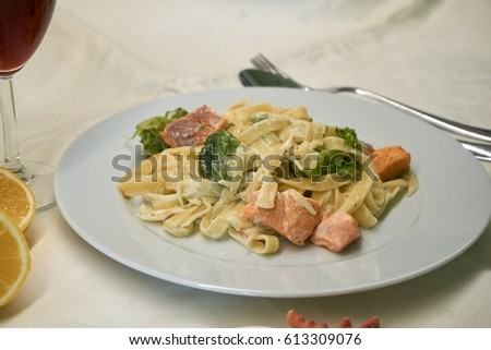 Pasta With Salmon And Broccoli In White Plate With Halves Of Lemon