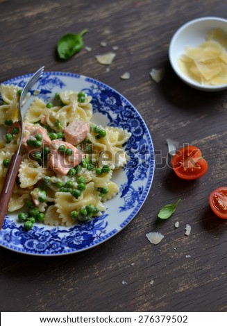 pasta with salmon and green peas in a creamy sauce in a vintage plate on a dark surface - stock photo