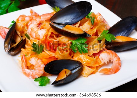 Pasta with shrimp, mussels, tomatoes and herbs - stock photo