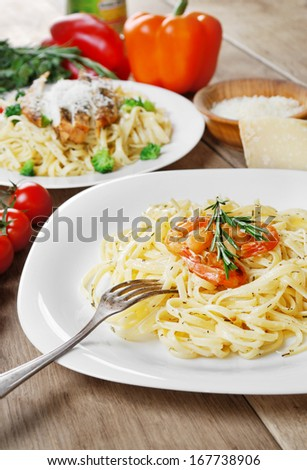 Pasta with shrimps and sauce with herbs on the wooden table