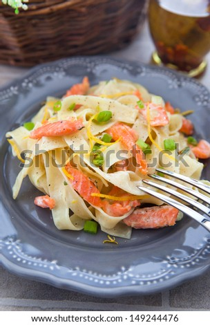 Pasta with smoked salmon and lemon zest on the gray plate on the stone table, close-up - stock photo