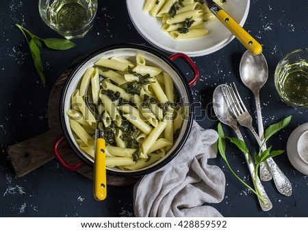 Pasta with spinach, blue cheese cream sauce on dark stone background - stock photo