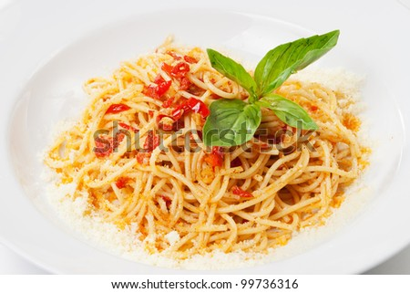 pasta with sweet bell pepper, basil leaf and  parmesan, on white plate - stock photo