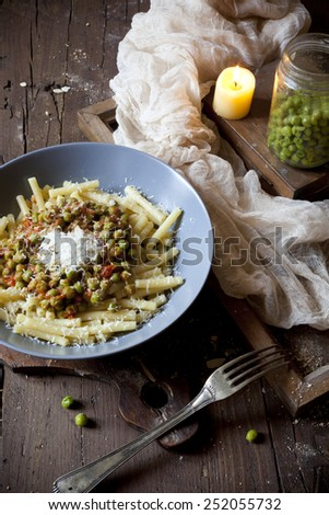 pasta with tomato and whole peas sauce on plate with parmesan cheese on rustic wooden table  - stock photo