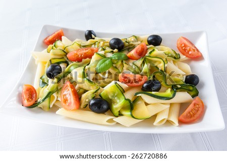 pasta with vegetables: zucchini, olives, tomatoes - stock photo