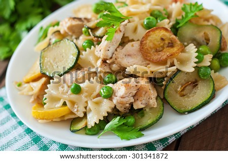 Pasta with zucchini, chicken and green peas - stock photo
