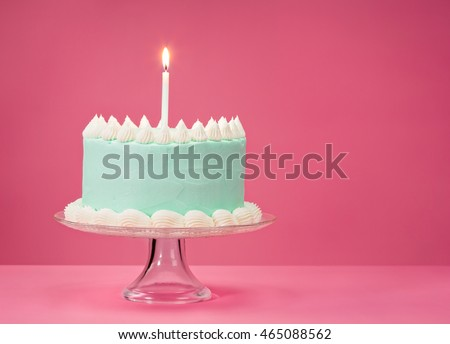Pastel blue birthday cake over pink background with one candle.