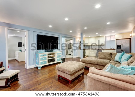 Pastel blue walls in basement living room interior with open floor plan. Large corner sofa with blue pillows and ottoman. Vintage white and blue TV cabinet. Northwest, USA