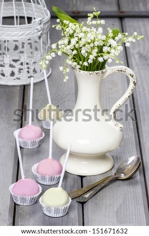 Pastel cake pops on rustic grey wooden table. Bouquet of lilly of the valley flowers in ceramic vase.