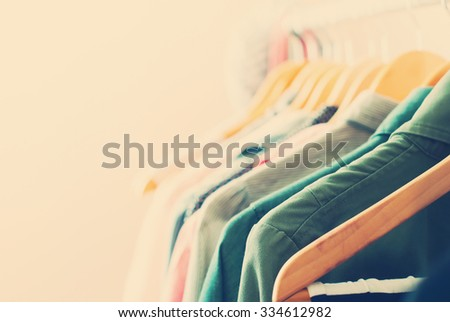 Pastel Color Clothes. Female Dresses on Open Clothes Rail. Toned image - stock photo