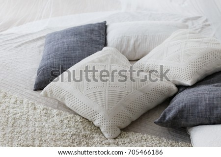 pastel color white and light grey cushions or pillows setting on bed with satin bedding