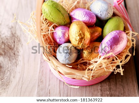 Pastel colored chocolate Easter eggs placed in straw nest in straw basket close up - stock photo