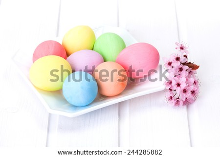 Pastel colored Easter eggs in white plate - stock photo