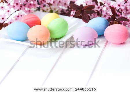 Pastel colored Easter eggs on white board - stock photo