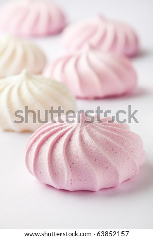 Pastel colored meringue on a white background - stock photo
