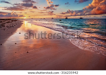 Pastel coloured sky and waters, at sunset, with boats in the background 2 - stock photo