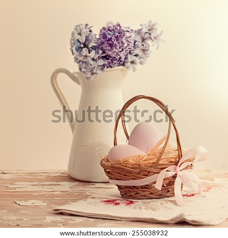 Pastel easter eggs in basket and flowers in jug,vintage style - stock photo