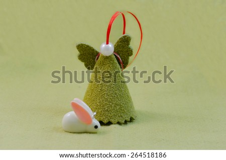 Pastel green background with handmade angel and tiny white Easter rabbit  - stock photo