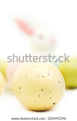 Pastel yellow speckled Easter egg up close with the Easter Bunny in the background watching over his batch of eggs.  - stock photo