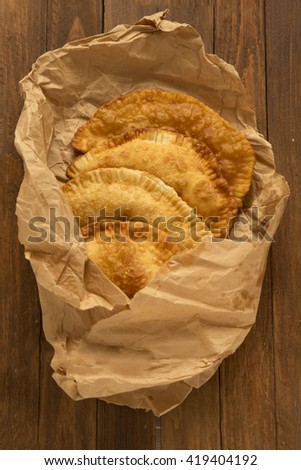 pasties in paper over wooden background - stock photo