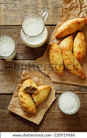 pasties stuffed meat and glass of milk on a dark wood background. tinting. selective focus on the meat - stock photo