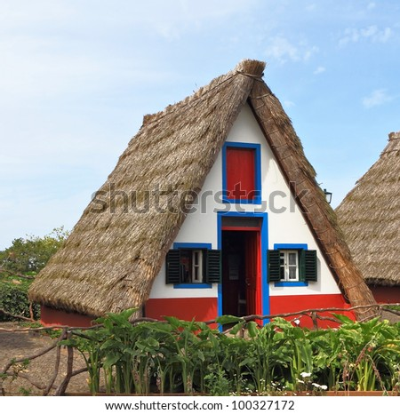 Pastoral landscape. Cosy chalet with a triangular thatched roof. Before the house - a green fence. Madeira, the city of Santana - stock photo
