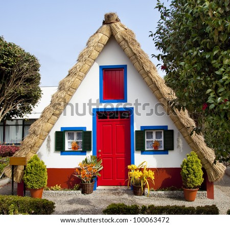 Pastoral landscape. Small rural house with a triangular thatched roof. The red door and small windows with shutters. Santana city, Madeira island,Portugal - stock photo
