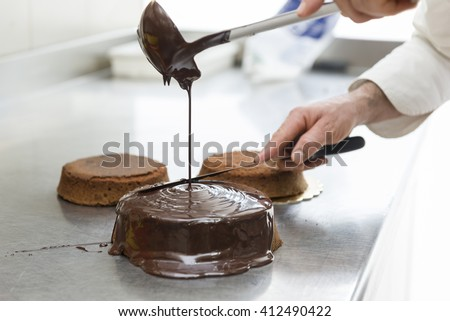 pastry chef covering cake with melted chocolate