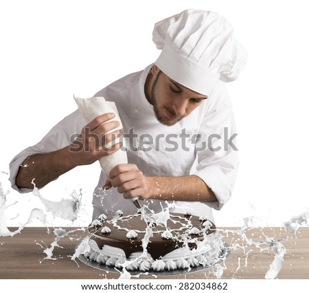Pastry chef decorates a cake with cream - stock photo
