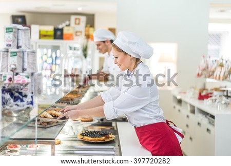 Pastry chefs working in a bar cafeteria - stock photo