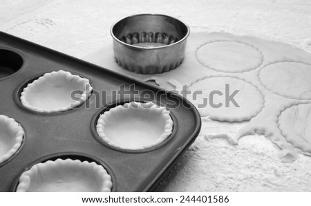 Pastry circles being cut and lining a metal bun tin for jam tarts - monochrome processing
