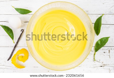 Pastry cream on white wood background. Preparation of sweet custard pastry cream in a bowl, top view.Pastry filling. - stock photo
