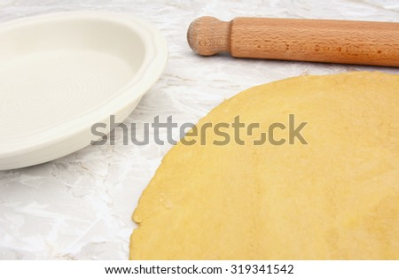 Pastry rolled out on work surface with wooden rolling pin next to empty pie dish