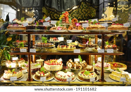 Pastry shop display window with variety of cakes. - stock photo
