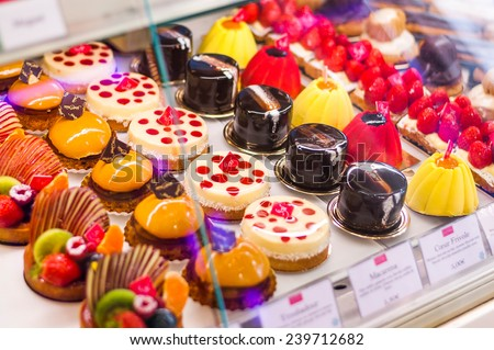 Pastry shop with variety of donuts, jelly beans, muffins, creme brulee, cakes with fruits and berries - stock photo