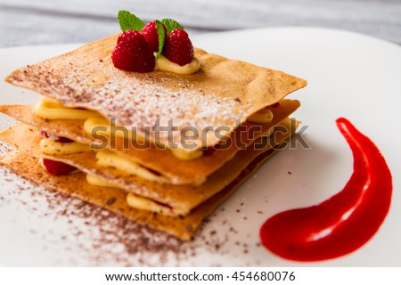 Pastry with leaves of mint. Red sauce and white powder. Dessert that looks appetizing. Raspberry millefeuille is ready.