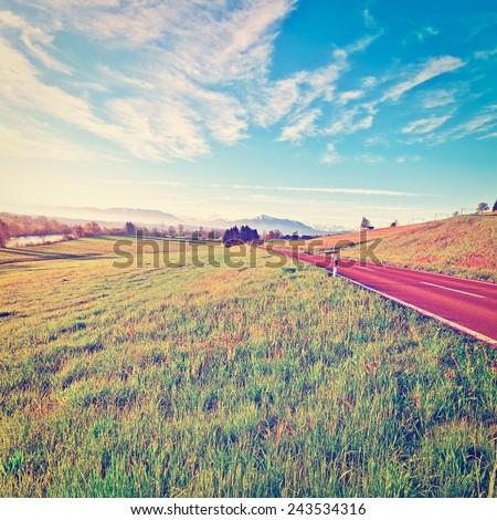 Pasture along the Irrigation Canal and Asphalt Road on the Background of the Snow-capped Alps in Switzerland, Instagram Effect - stock photo
