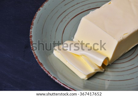 Pat of fresh farm butter on a butter dish with a knife to use as a spread or cooing ingredient, overhead view on a slatted wooden table - stock photo