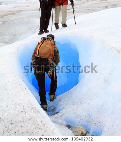 PATAGONIA - CIRCA 2009: An unidentified man is about to enter to a tunnel naturally carved in a glacier on Circa 2009 in Patagonia, South America.