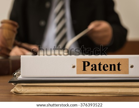 Patent document folder with lawyer work at law firm. Concept of complaints about patent lawsuit.