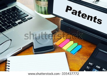 Patents- Ring Binder on Office Desktop with Office Supplies. Business Concept on Toned and Blurred Background - stock photo