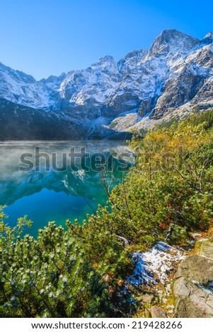 Path along Morskie Oko lake in autumn colours with fresh snow covered peaks, High Tatra Mountains, Poland - stock photo