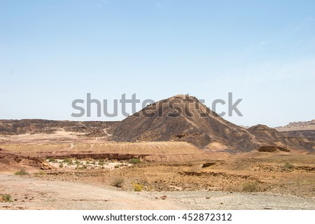 Path in the desert of colored rocks - stock photo