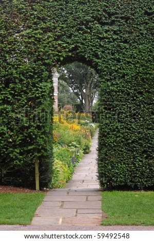 Path leading through an archway in a hedgerow with Flower borders beyond - stock photo