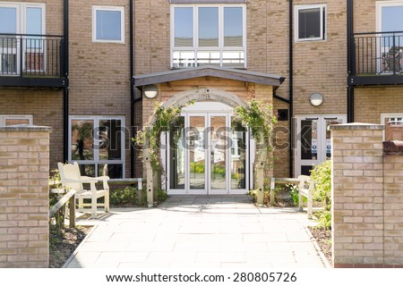 Path leading to Arched Pergola in front of automatic doors - stock photo