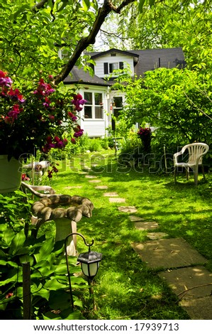 Path of steeping stones leading to a house in lush green garden - stock photo